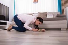 Donna che esamina il pavimento di legno duro tramite la lente d'ingrandimento immagini stock libere da diritti