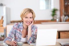 Donna che esamina il suo computer portatile Immagini Stock