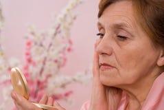 Donna che esamina il suo fronte nello specchio Immagini Stock