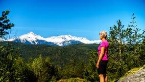 Donna che esamina la catena montuosa di Tantalus con i picchi innevati della montagna di Alpha Mountain, di Serratus e di Tantalu Immagine Stock Libera da Diritti