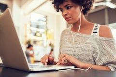 Donna che esamina lavorare occupato al computer portatile il caffè Immagine Stock