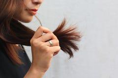 Donna che esamina le doppie punte nocive di capelli, concetto di Haircare immagini stock libere da diritti