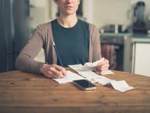 Donna che esamina le ricevute a casa Fotografia Stock