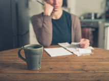 Donna che esamina le ricevute e che mangia tè Fotografia Stock