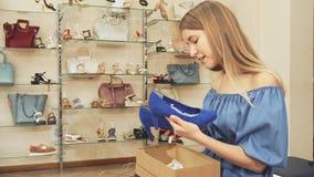 Donna che esamina le sue nuove scarpe e la macchina fotografica video d archivio
