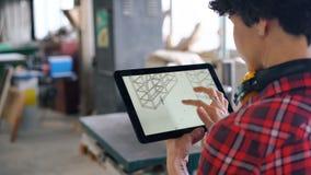 Donna che esamina lo schermo della compressa che controlla progettazione della mobilia in officina di legno stock footage