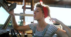 Donna che esamina lo specchio di automobile mentre avendo gomma da masticare 4k video d archivio