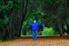 Donna che esamina macchina fotografica, armi largamente, stante fra gli alberi di cedro sull'isola di Mackinac immagini stock