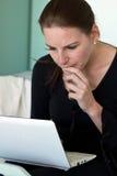 Donna che esamina meditatamente lo schermo del computer portatile Immagini Stock Libere da Diritti