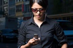 Donna che esamina messaggio di testo Fotografia Stock