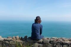 Donna che esamina oceano di nuovo alla macchina fotografica, giorno soleggiato fotografie stock libere da diritti