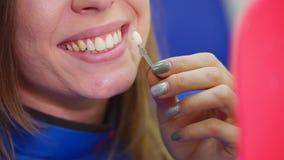 Donna che esamina risultato dei denti che imbiancano nella clinica dentaria archivi video
