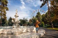 Donna che esamina ruota panoramica nel parco di autunno Fotografia Stock