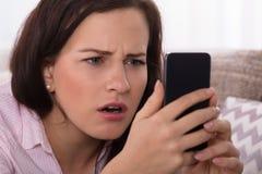Donna che esamina smartphone fotografia stock