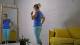 Donna che esamina specchio imbarazzato di peso in eccesso stock footage