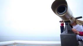 Donna che esamina tramite il binocolo turistico la riva di mare ricorso video d archivio