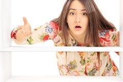 Donna che esamina un frigorifero vuoto Fotografie Stock