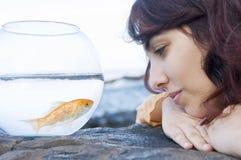 Donna che esamina un pesce in una ciotola Fotografia Stock