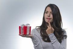 Donna che esamina un regalo con uno sguardo imbarazzato Immagini Stock