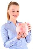 Donna che esamina una banca piggy Immagini Stock