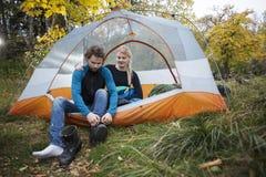 Donna che esamina uomo che dura facendo un'escursione stivale in tenda fotografia stock