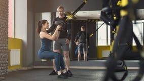 Donna che esegue addestramento di TRX nella palestra Fotografia Stock