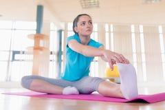 Donna che esegue allungando esercizio nella palestra Fotografie Stock