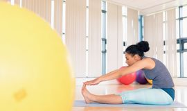 Donna che esegue allungando esercizio nella palestra Fotografia Stock