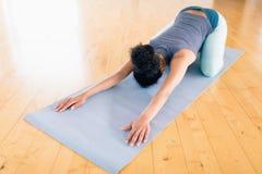 Donna che esegue allungando esercizio nella palestra Fotografie Stock Libere da Diritti