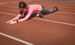 Donna che esegue allungando esercizio su una pista di corsa Immagini Stock Libere da Diritti