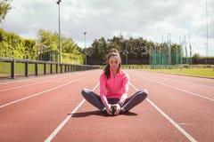 Donna che esegue allungando esercizio su una pista di corsa Immagine Stock
