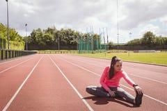 Donna che esegue allungando esercizio su una pista di corsa Fotografia Stock Libera da Diritti