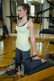 Donna che esegue allungando esercizio sul riformatore Immagini Stock