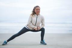 Donna che esegue allungando esercizio sulla spiaggia Fotografia Stock Libera da Diritti