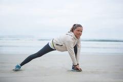 Donna che esegue allungando esercizio sulla spiaggia Fotografia Stock