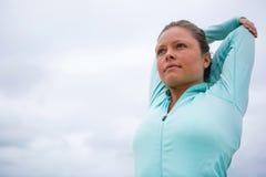 Donna che esegue allungando esercizio sulla spiaggia Fotografie Stock