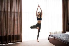 Donna che esegue posa di yoga sul pavimento nel concetto di casa di addestramento di Pilates, di yoga e di sport Immagine Stock