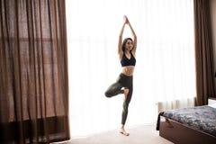 Donna che esegue posa di yoga sul pavimento nel concetto di casa di addestramento di Pilates, di yoga e di sport Immagini Stock Libere da Diritti