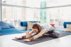 Donna che esegue posa di yoga sulla stuoia, sullo stile di vita sano e sul concetto di forma fisica Fotografia Stock