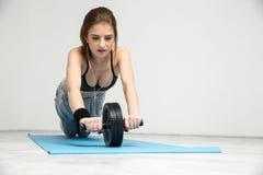Donna che esercita la ruota addominale di allenamento di forma fisica Immagini Stock