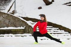 Donna che esercita le gambe fuori durante l'inverno Immagine Stock