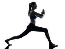 Donna che esercita posizione del guerriero di yoga Fotografia Stock