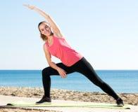 Donna che esercita yoga alla spiaggia del mare Fotografia Stock