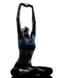 Donna che esercita yoga che medita seduta allungando siluetta Immagine Stock Libera da Diritti