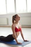 Donna che esercita yoga di posa della cobra di saluto del sole Fotografie Stock