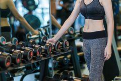 Donna che fa addestramento del muscolo alla palestra Atleta che risolve alla sfuocatura di forma fisica della palestra Immagini Stock