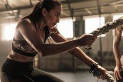 Donna che fa addestramento di forza con le corde di battaglia fotografia stock