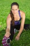 Donna che fa allungamento dell'esercizio prima degli sport su un prato Fotografia Stock