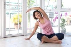 Donna che fa allungamento della sua indietro esercitazione. Immagini Stock