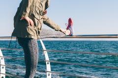 Donna che fa allungamento di mattina sulla costa Fotografie Stock Libere da Diritti